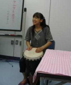 ケニア太鼓を披露する講師の高見さん。