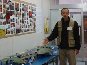 旅の写真と手づくりの日本地図の前で話をする郭さん