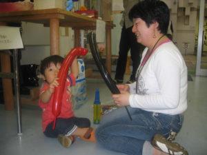 子どもとスタッフが一緒にバルーンアートをしています。