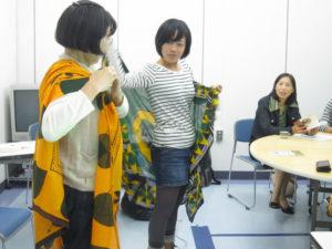 アフリカの布(カンガ)の使い方を説明を受けています。