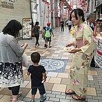 通りを行く人にポップコーンの試食をすすめる学生